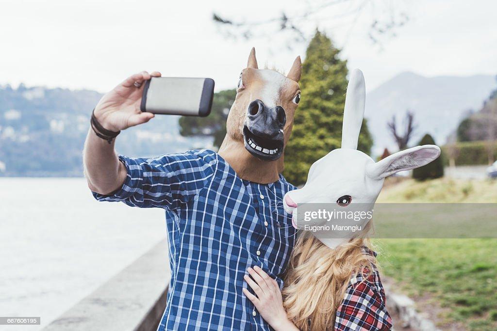 Couple wearing horse and rabbit masks taking smartphone selfie, Lake Como, Italy : Stock Photo