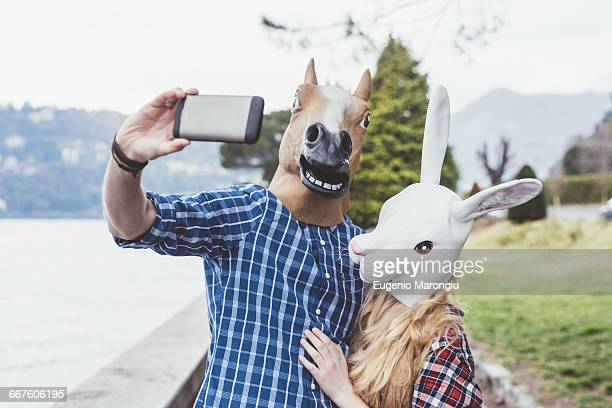couple wearing horse and rabbit masks taking smartphone selfie, lake como, italy - freaky couples stock photos and pictures