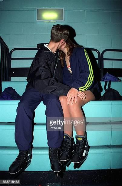 A couple wearing ice skates kissing at an ice rink UK 2000s