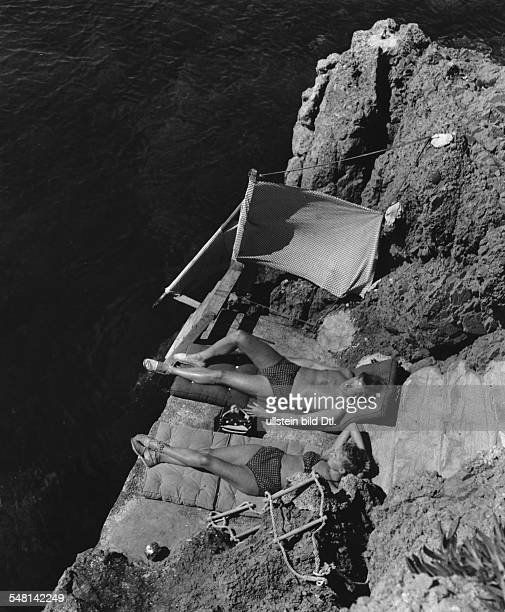 Couple wearing identical swimwear sunbathing on rocks at Cap Roux Cote d'Azur 1939 Photographer Regine Relang Published by 'Die Dame' 12/1939 Vintage...