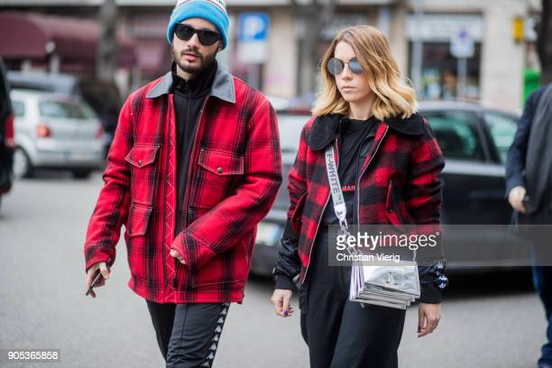 A couple wearing lumberjack print jacket silver off white bag is seen outside Armani during Milan Men's Fashion Week Fall/Winter 2018/19 on January...