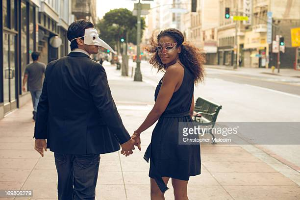 Couple wearing mask hold hands and walk