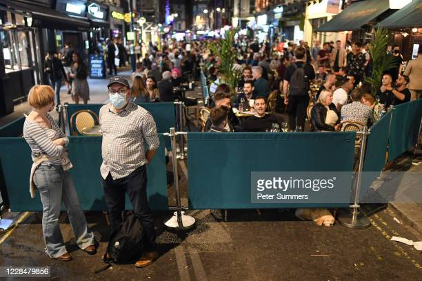 Couple wearing masks are seen in front of crowds on September 12, 2020 in London, England. From Monday, September 14, groups of more than six will be...