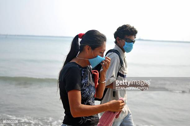 A couple wearing masks for protection against exposure to influenza A virus walk along the beach in Veracruz Mexico on May 02 2009 Thousands of...