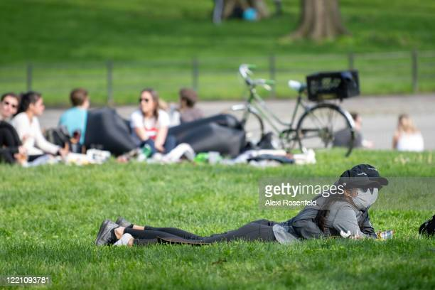 A couple wearing masks lie together in Central Park as temperatures rose amid the coronavirus pandemic on April 25 2020 in New York City United...