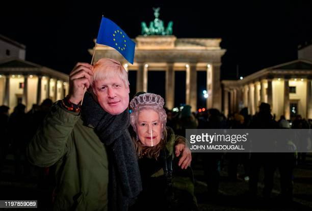 Couple wearing masks of Britain's Prime Minister Boris Johnson and Britain's Queen Elizabeth II wave an EU flag during a flashmob to mark Brexit in...