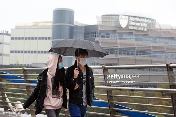 Couple wearing masks walk close to Northumbria University in Newcastle-upon-Tyne, north-east England on October 3, 2020 as many students self-isolate...