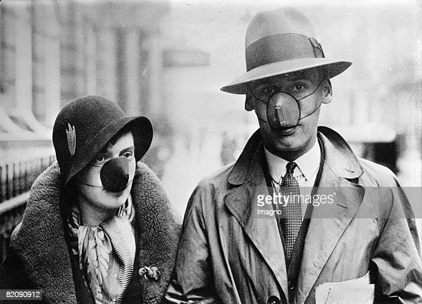 Couple wearing masks with disinfecting cotton wool, in order to protect themself against a flu infection, England, Photograph, Oct, 14th 1932 [Ein...