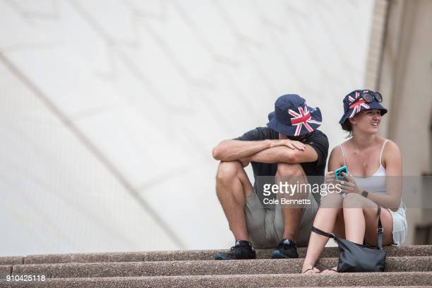 A couple wearing matching Australia Day hats wait out the heat on the steps of the Opera House on January 26 2018 in Sydney Australia Australia Day...