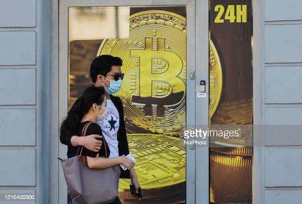 A couple wearing medical masks passes in front of a Bitcoin exchange shop in Krakow's city center On Saturday April 18 in Krakow Poland