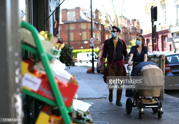 Couple wearing PPE , including a face mask as a precautionary measure against COVID-19, walk past closed shops on Englands Lane in north London on...