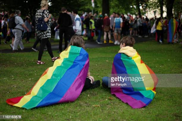 Couple wearing pride flags sit on the grass as thousands of people gather to take part in the Newcastle Pride Festival parade on July 20, 2019 in...