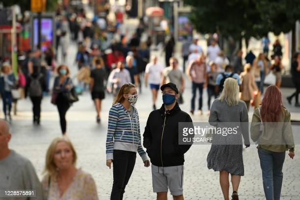 Couple wearing protective face coverings chat in the street in Liverpool city centre, north-west England on September 18, 2020 after the British...