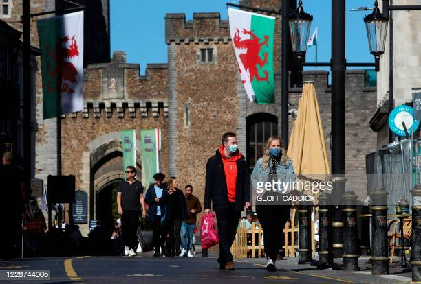 Couple wearing protective face coverings, walk through the city in the late summer sunshine in Cardiff, south Wales on September 27 during...