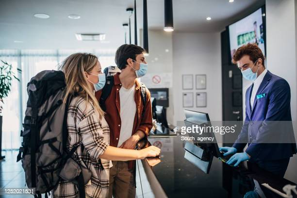 couple wearing protective face mask while doing check-in at the hotel reception - hotel stock pictures, royalty-free photos & images