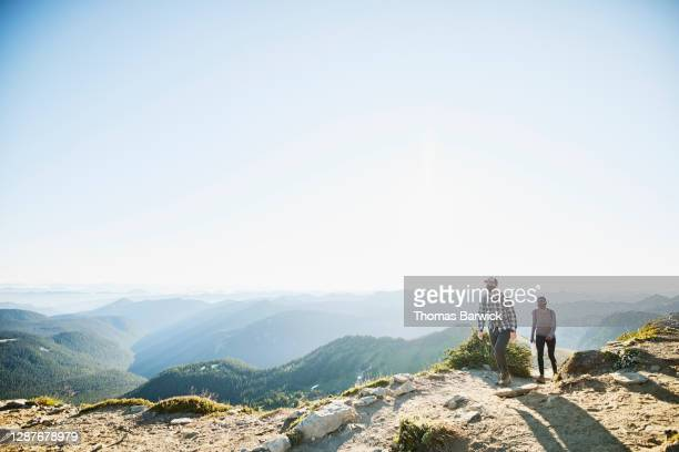 couple wearing protective face masks on sunrise hike in mountains - travel stock pictures, royalty-free photos & images
