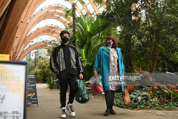 Couple wearing protective face masks, walk through The Winter Garden in Sheffield, in northern England on October 21 prior to further lockdown...