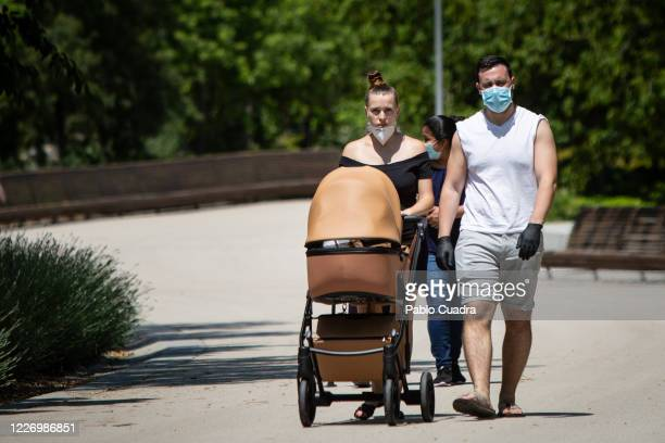 Couple wearing protective face masks walks pushing a stroller through the Madrid Rio park after 72 days closed due to the coronavirus crisis, once...