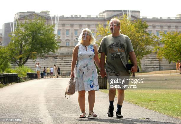 Couple wearing protective face shields walk in front of Buckingham Palace in St James Park as the heatwave continues in London on August 8, 2020.