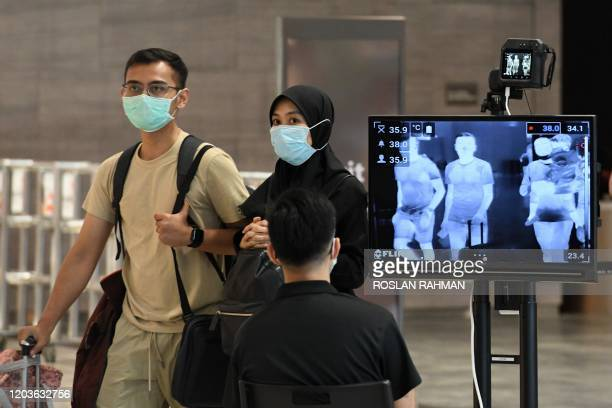 Couple, wearing protective facemasks amid fears about the spread of the COVID-19 novel coronavirus, walk past a temperature screening check at Changi...