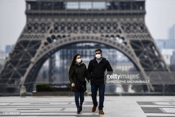 Couple wearing protective mask walks by the Esplanade du Trocadero square near the Eiffel Tower in Paris, on March 18 a day after a strict lockdown...