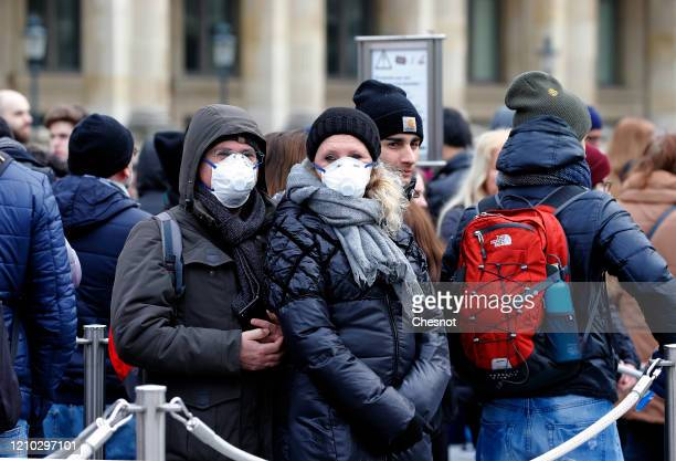 A couple wearing protective masks are lining up in front of the Louvre Museum as the museum was closed for a staff meeting about the coronavirus...