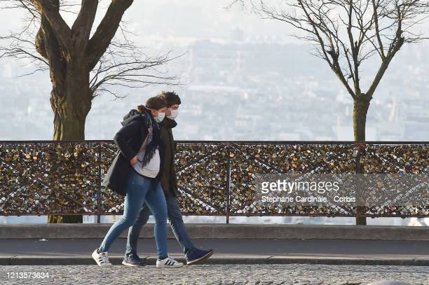 A couple wearing protective masks are seen on the third day after the announcement by French President Emmanuel Macron of the confinement of the...