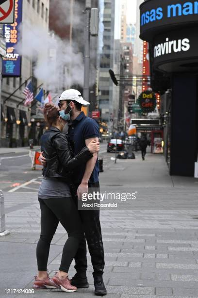 A couple wearing protective masks embrace in Times Square amid the coronavirus pandemic on April 05 2020 in New York City COVID19 has spread to more...