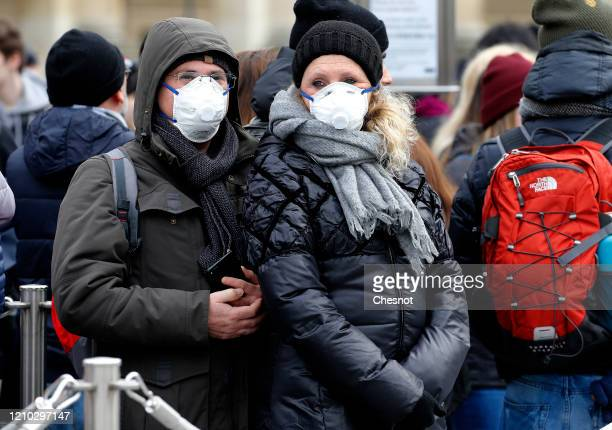 A couple wearing protective masks is lining up in front of the Louvre Museum as the museum was closed for a staff meeting about the coronavirus...