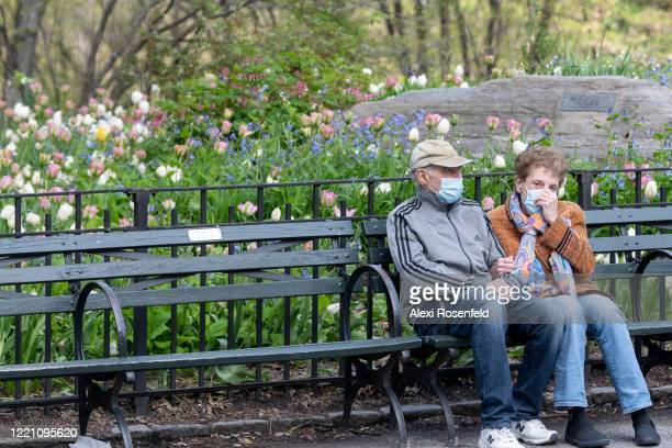 A couple wearing protective masks sit together in Central Park as temperatures rose amid the coronavirus pandemic on April 25 2020 in New York City...