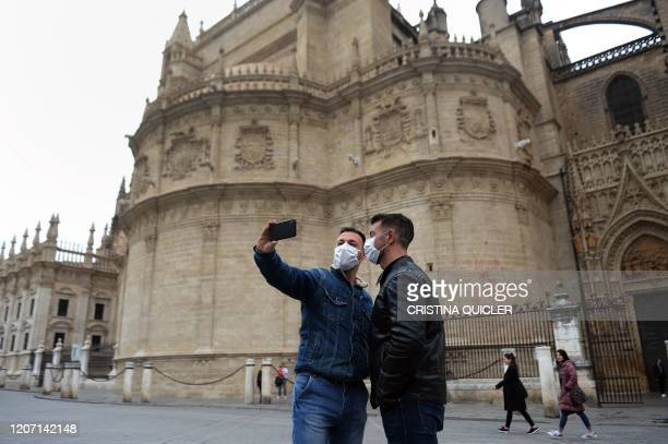 Couple, wearing protective masks, take a selfie photo in front of the Cathedral in Seville, on March 14, 2020. - Seville decided today to cancel its...