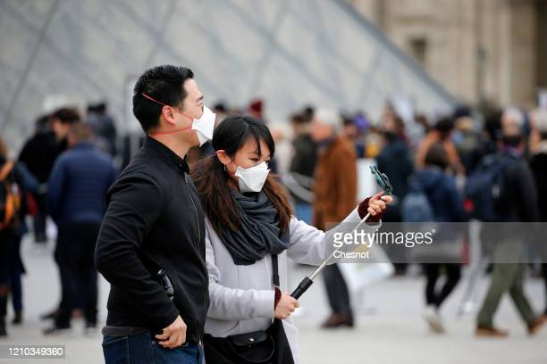 A couple wearing protective masks takes a selfie in front of the Louvre Museum as the museum was closed for a staff meeting about the coronavirus...