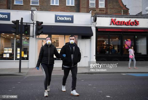 A couple wearing protective masks walk across a street in Clapham on March 20 2020 in London England Coronavirus has spread to at least 182 countries...