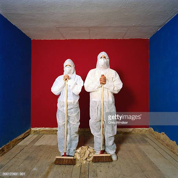 Couple wearing protective suits holding brooms beside pile of debris