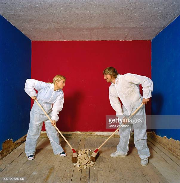 Couple wearing protective suits sweeping debris into centre of room