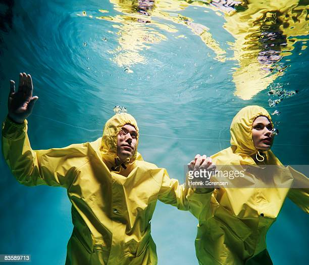 Couple wearing raincoats under water