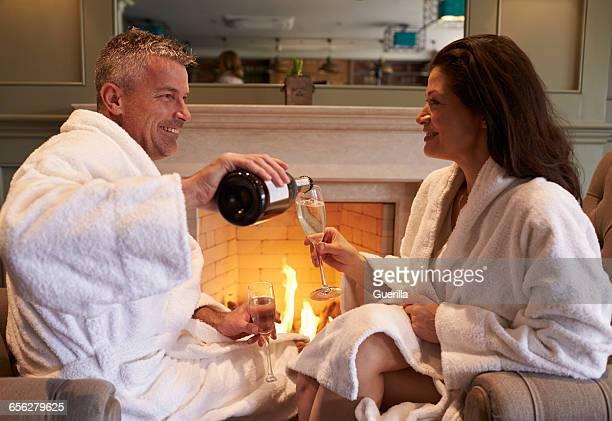 Couple Wearing Robes Relaxing On Hotel Spa Break