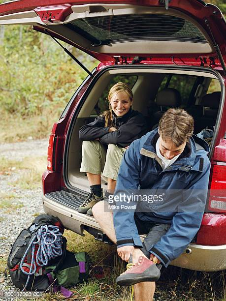 couple wearing rock climbing gear, sitting in back of suv, portrait - climbing equipment stock pictures, royalty-free photos & images