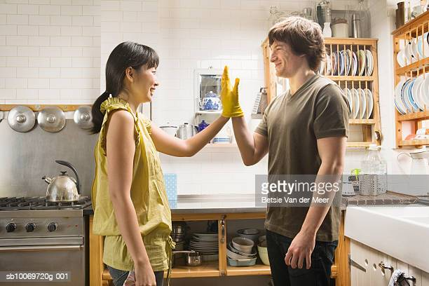 Couple wearing rubber gloves touching hands in kitchen