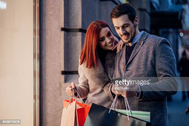 Couple wearing shopping bags and looking at phone