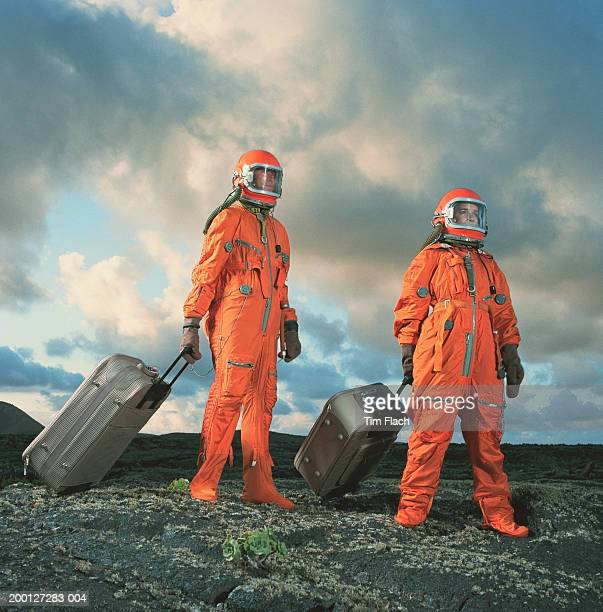 Couple wearing space suits pulling luggage across rugged landscape
