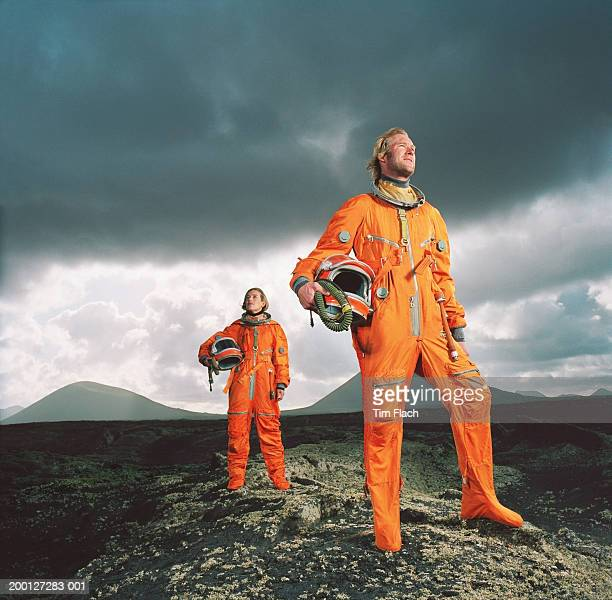 Couple wearing space suits standing on rugged landscape, low angle