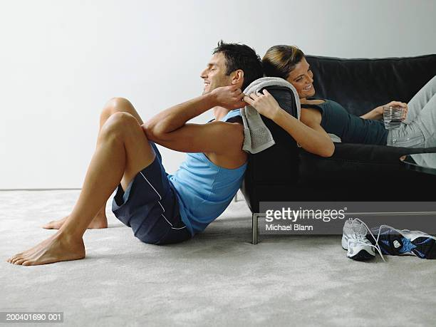 couple wearing sports clothes resting in living room, smiling - ショートパンツ ストックフォトと画像