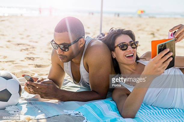 Couple wearing sunglasses relaxing at beach