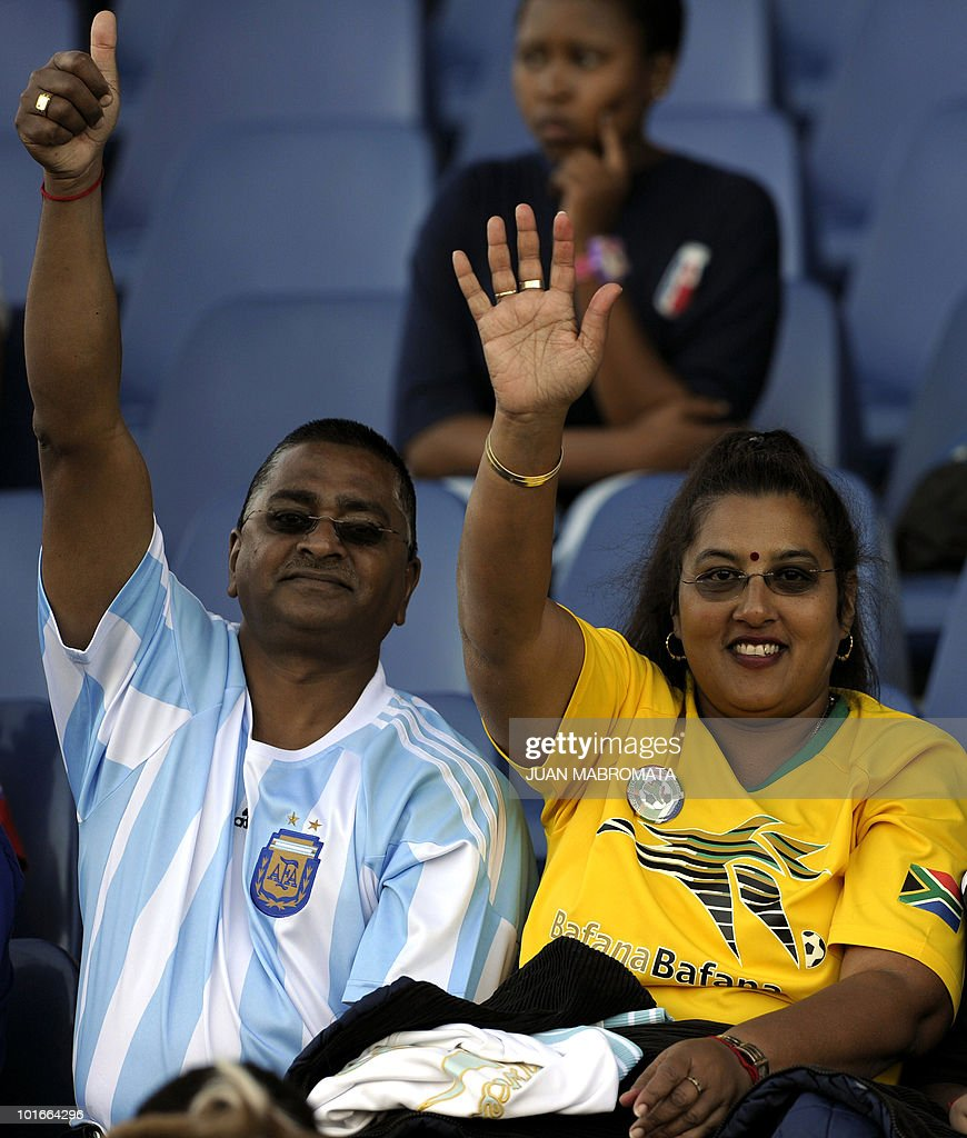 A couple wearing the jerseys of Argentina's (L) and South Africa's (R) national teams wave as they attend Paraguay's training session at Harry Gwala stadium in Pietermaritzburg on June 6, 2010 ahead of the 2010 World Cup in South Africa.