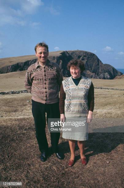 Couple wearing traditional Fair Isle pattern knitwear, Fair Isle, Shetland Islands, Scotland, June 1970. Behind them is the headland of Sheep Rock.