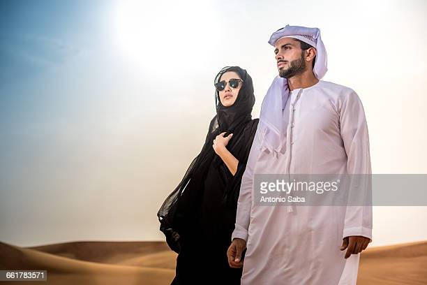 couple wearing traditional middle eastern clothes in desert, dubai, united arab emirates - united arab emirates stock pictures, royalty-free photos & images