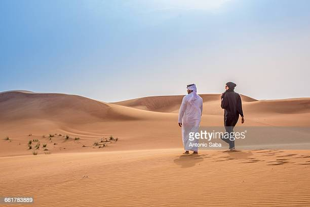Couple wearing traditional middle eastern clothes walking in desert, Dubai, United Arab Emirates