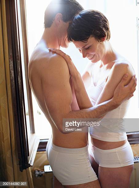 couple wearing underwear embracing by window - frau in slip stock-fotos und bilder