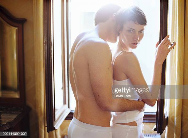 Couple wearing underwear embracing by window, portrait of woman